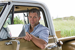 handsome man in a vintage truck in the Hamptons