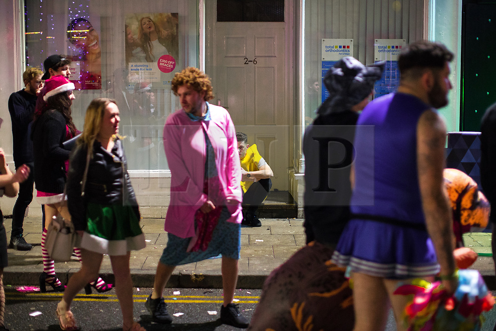 © Licensed to London News Pictures . 27/12/2017. Wigan, UK. A man dressed as a banana sits in a doorway. Revellers in Wigan enjoy Boxing Day drinks and clubbing in Wigan Wallgate . In recent years a tradition has been established in which people go out wearing fancy-dress costumes on Boxing Day night . Photo credit: Joel Goodman/LNP