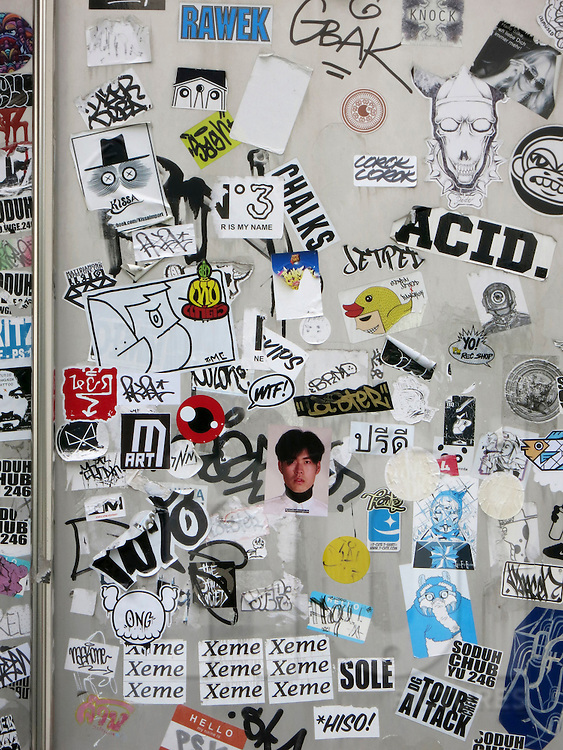 A sticker-covered wall along a street in Bangkok, Thailand, Southeast Asia