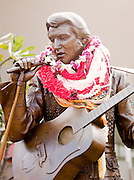 Bronze statue of Elvis Preley, decorated with garlands, on O'Ahu, Hawai'i