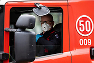 Fire crews wearing facemasks are seen driving away from the Flemington housing commission tower amid a full and total lockdown of 9 housing commission high rise towers in North Melbourne and Flemington during COVID-19 on 5 July, 2020 in Melbourne, Australia. After 108 new cases where uncovered overnight, the Premier Daniel Andrews announced on July 4 that effective at midnight last night, two more suburbs have been added to the suburb by suburb lockdown being Flemington and North Melbourne. Further to that, nine high rise public housing buildings in these suburbs have been placed under hard lockdown for a minimum of five days, effective immediately.  Residents in these towers will not be allowed to leave their units for any reason. Police will be stationed at every entry and exit point, every level, and they will also surround these locations preventing any movement in, or out. There is a total of 1354 units and over 3000 residents living in these buildings including the states most vulnerable people. These new restrictions will remain in place for fourteen days with fears of further lockdowns to come. The Government have stressed that if Victorians do not follow the basic COVIDSafe rules, the whole state will go back in to lockdown. (Image by Dave Hewison/ Speed Media)