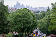 With the skyscrapers of the City of London, the capital's financial district, in the distance, rush-hour traffic builds at the bottom of Sydenham Hill, on 15th June 2021, in south London, England.