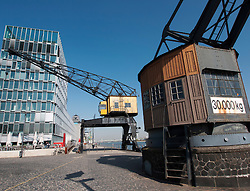 Modern new buildings and old heritage dock crane on riverside at Rheinaufhafen property development in Cologne Germany