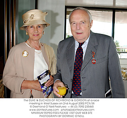 The DUKE & DUCHESS OF RICHMOND & GORDON at a race meeting in West Sussex on 2nd August 2002.	PCN 58