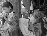 Old men, victims of the Khmer Rouge, attend a symposium at a local Buddhist temple to better understand the effects that still haunt their lives.  Children who came with their parents seem less interested.  Studies of survivors of the Khmer Rouge era confirm that most suffer post-traumatic stress syndrome and the likelihood that their offspring will inherit the condition as well.
