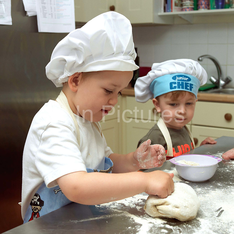 Two young boys making bread in the kitchen of Little Green Rascals Children's Organic Day Nursery, nr Elvington, York, North Yorkshire, UK. Little Green Rascals is a children's day nursery that opened in York in July 2009. It is the first fully organic day nursery in the North of England and has been awarded the Soil Association's Gold Catering Mark for the last four years.