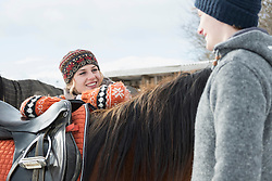 Young couple talking to each other and standing with horse, Bavaria, Germany