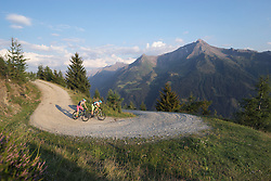 Two mountain bikers riding on dirt track in alpine landscape, Zillertal, Tyrol, Austria