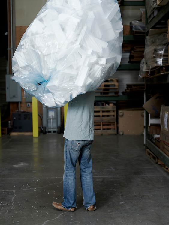 Man with large bag of recycled styrofoam on shoulder standing in warehouse.