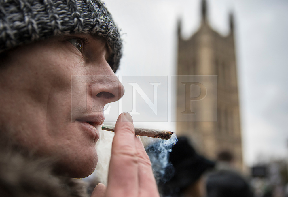 © Licensed to London News Pictures. 23/02/2018. London, UK. A protestor smokes a joint in sight of Parliament during a demonstration in support of cannabis for medicinal use - as MPs debate it's use in The House of Commons. Photo credit: Peter Macdiarmid/LNP