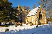 Winter scene churchyard snow and gravestones, village church Yatesbury, Wiltshire, England, UK