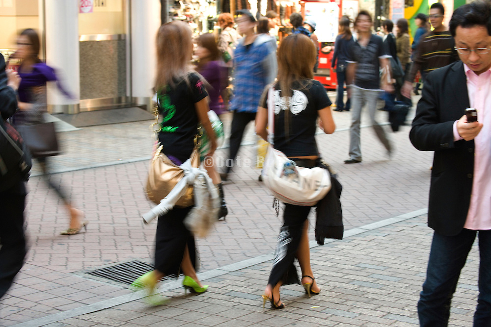 two fashionabley dressed young woman walking through the Shibuya district of Tokyo