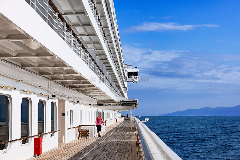 Vacationers exercise on a cruise ship jogging track.