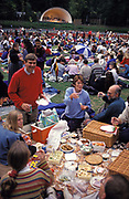 Crowds enjoy picnic spreads before an outdoor concert at Kenwood House, North London, on 18th May 1995, in London, England. Set in Hampstead Heath, these grounds were remodelled by Robert Adam between 1764 and 1779. English Heritage host Summer concerts here and families and music fans spend war summer evenings listening to opera, classical or series of themed performances by visiting artists and groups. Here is also the source of one of Londons lost rivers, The Fleet which rises here and flows downhill into the city where it becomes part of the sewer system, emerging in the Thames at Blackfriars.