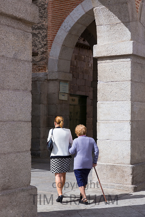 Local people, possibly elderly mother and daughter, strolling in old town of Avila, Spain