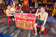 "19 AUGUST 2014 - BANGKOK, THAILAND:  Performers with the Lehigh Leng Kaitoung Opera troupe relax on stage before a show at the Chaomae Thapthim Shrine, a small Chinese shrine in a working class neighborhood of Bangkok. The performance was for Ghost Month. Chinese opera was once very popular in Thailand, where it is called ""Ngiew."" It is usually performed in the Teochew language. Millions of Chinese emigrated to Thailand (then Siam) in the 18th and 19th centuries and brought their culture with them. Recently the popularity of ngiew has faded as people turn to performances of opera on DVD or movies. There are still as many 30 Chinese opera troupes left in Bangkok and its environs. They are especially busy during Chinese New Year and Chinese holiday when they travel from Chinese temple to Chinese temple performing on stages they put up in streets near the temple, sometimes sleeping on hammocks they sling under their stage. Most of the Chinese operas from Bangkok travel to Malaysia for Ghost Month, leaving just a few to perform in Bangkok.        PHOTO BY JACK KURTZ"