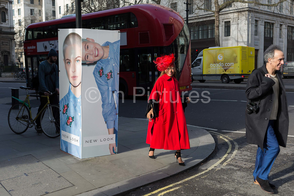A stylish woman walks towards the entrance of London Fashion Week in the Strand, on 17th Febriary 2017, in London, England, United Kingdom. London Fashion Week is a clothing trade show held in London twice each year, in February and September. It is one of the Big Four fashion weeks, along with the New York, Milan and Paris. The fashion sector plays a significant role in the UK economy with London Fashion Week alone estimated to rake in £269 million each season. The six-day industry event allows designers to show their collections to buyers, journalists and celebrities and also maintains the city's status as a top fashion capital.
