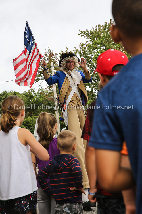 (9/2/19, MARLBOROUGH, MA) A stilt walker waves the American Flag and entertains children during the 68th annual Labor Day Parade along  Broad St. in Marlborough on Monday. [Daily News and Wicked Local Photo/Dan Holmes]
