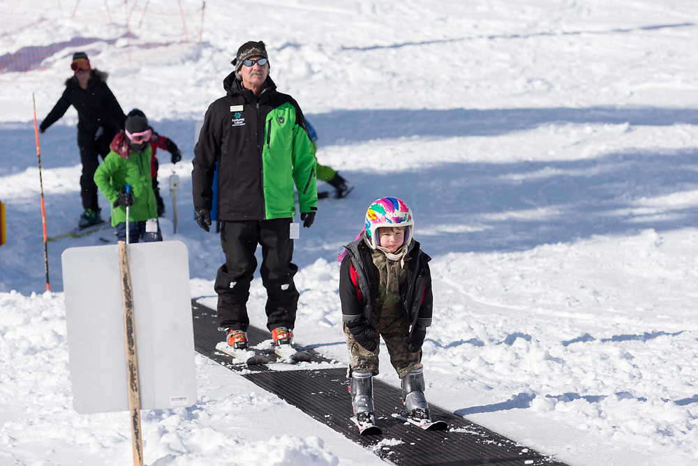 Kids and ski instructor on a magic carpet ski lift at Anthony Lakes Mountain Resort in Northeast Oregon.
