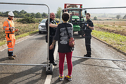 Offchurch, UK. 24th August, 2020. A police officer hands an acorn from a mature oak tree just felled alongside the Fosse Way to an anti-HS2 activist who had occupied a trailer being used to transport wood chip in order to try to prevent or delay the felling of the tree in connection with the HS2 high-speed rail link. The controversial HS2 infrastructure project is currently expected to cost £106bn and will destroy or significantly impact many irreplaceable natural habitats, including 108 ancient woodlands.