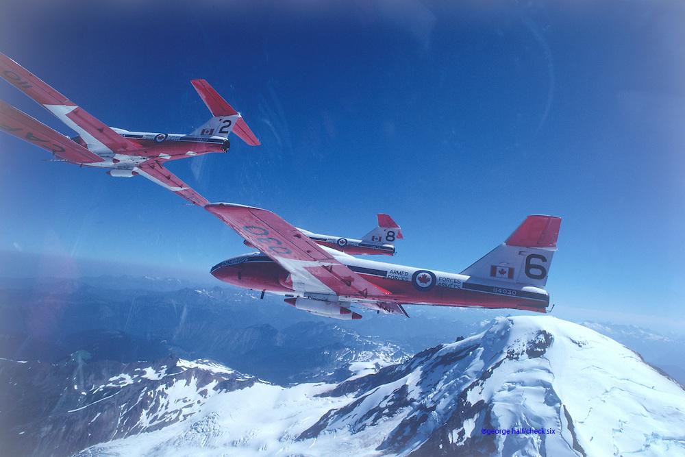 Canadian Snowbirds flying over mountain peak