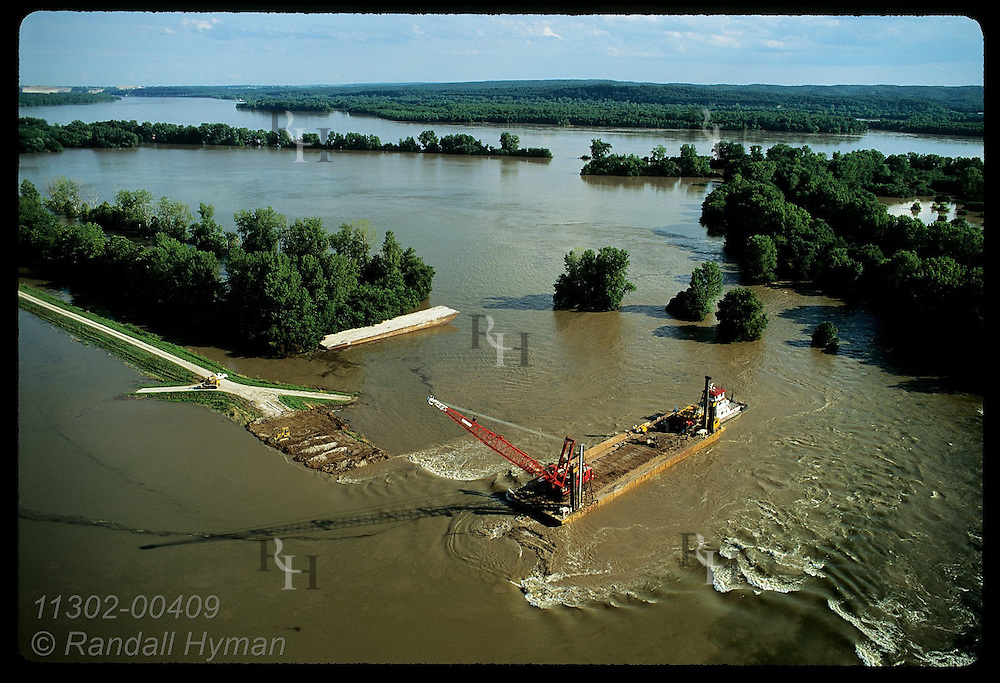 Aerial:crane on barge cuts hole in Mississippi's levee to drain flood; 8/3/93, Prairie du Rocher Illinois