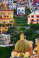 """""""Evening falls on the cross and dome of Santa Maria Assunta in Positano"""" ...<br /> <br /> I never ventured to attempt many photos in the hot daylight sun of Italy; however, as the sun dropped down behind the cliffs of Positano in early evening…the lighting on the picturesque Amalfi village brought out the depth of color and highlighted the plush vegetation. Around 5:00pm, I positioned the camera at the edge of the opposing cliff to frame this image allowing the colors to derive their true spectrum of light and power. The focal point of most views of Positano is the church of Santa Maria Assunta. The colorful dome is made of majolica tiles which are very prominent on the Amalfi Coast, and the church contains a thirteenth-century Byzantine icon of the legendary Black Madonna."""