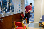 A prisoner watches his family leave after a visit. HMP/YOI Portland, Dorset. A resettlement prison with a capacity for 530 prisoners. Dorset, United Kingdom.