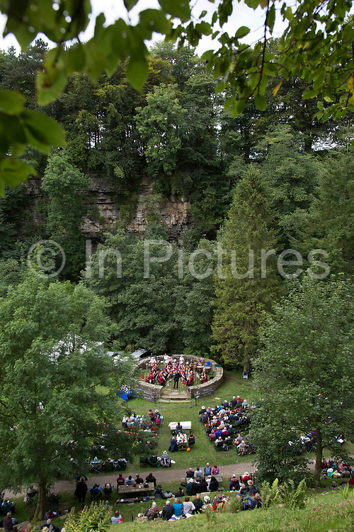 Audience at the Hardraw Scaur Brass Band Festival, high up on the hill looking down at the band stand amongst the landscape. Organised by the Yorkshire and Humberside Brass Band Association, the competition is Britain's second oldest outdoor contest and takes place annually in Hardraw Scar in Wensleydale, North Yorkshire, England, UK. The area, a natural amphitheatre, attracts bands from all over the North of England and is a popular event amongst players and audiences alike.