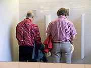 two man standing in front of urinals