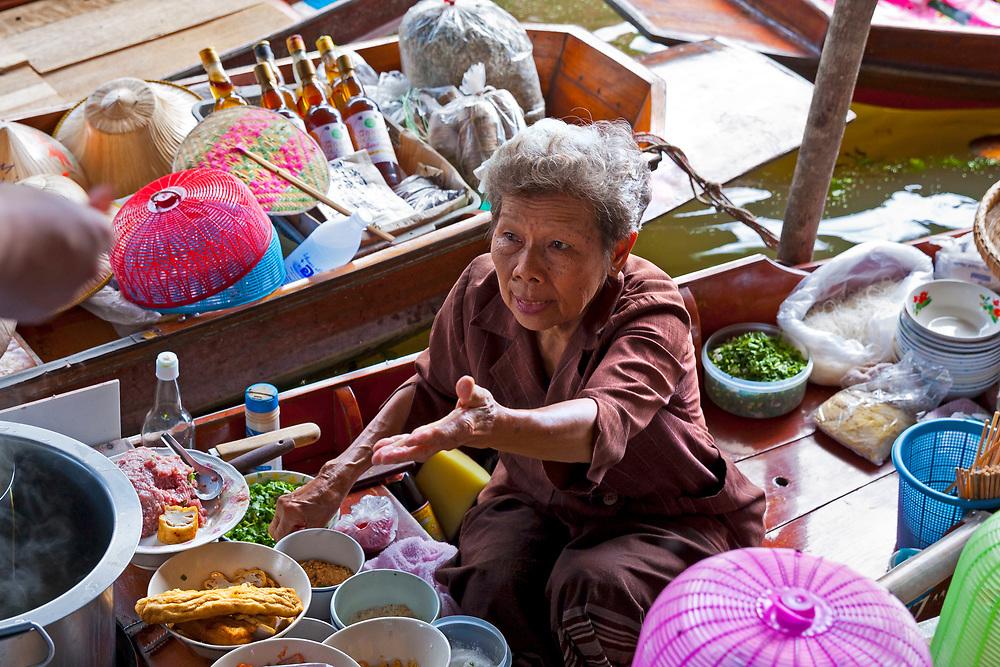 Elderly female food vendor cooking food at the Damnoen Saduak Floating Market, Thailand, SE Asia