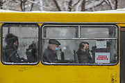"A sign (bottom right of the window) says ""wear a mask to save lives"" in an Armenian public transport yellow bus, while a person wearing a face surgical protective mask is seen sat through the misty glass due to low temperatures of cold and snowy weather in the Armenian capital Yerevan on Wednesday, Jan 20, 2021. According to John Hopkins University, Coronavirus death rates in Armenia reached up to 164,912 with over 3,000 deaths. (Photo/ Vudi Xhymshiti)"