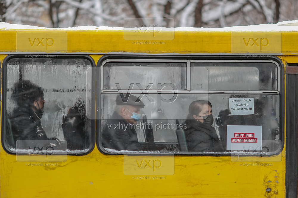 """A sign (bottom right of the window) says """"wear a mask to save lives"""" in an Armenian public transport yellow bus, while a person wearing a face surgical protective mask is seen sat through the misty glass due to low temperatures of cold and snowy weather in the Armenian capital Yerevan on Wednesday, Jan 20, 2021. According to John Hopkins University, Coronavirus death rates in Armenia reached up to 164,912 with over 3,000 deaths. (Photo/ Vudi Xhymshiti)"""