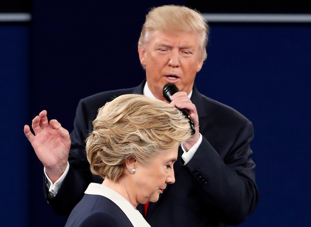Republican U.S. presidential nominee Donald Trump speaks as Democratic U.S. presidential nominee Hillary Clinton listens during their presidential town hall debate at Washington University in St. Louis, Missouri, U.S., October 9, 2016.    REUTERS/Jim Young