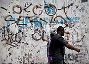 Men walk past a hoarding covered in Grafitti at Elephant and Castle in South London.