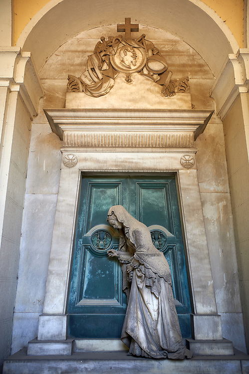 Picture and image of the stone sculpture of a  mourning widow who is bringing a crown and knocking on a sepulcher's bronze door, which holds the bas relief of an hourglass, a classic symbol of the passing of time. This theme of the sorrowful survivor in front of the sepulcher's door comes from the Monument dedicated to Maria Christina, Duchess of Teschen, Maria Theresa of Austria's daughter, a neoclassical sculpture. In this version the widow is wearing fashionable clothes, which have been accurately represented, and her openwork shawl. Sculptor G. B. Cevasco 1875. Section A, no 38, The monumental tombs of the Staglieno Monumental Cemetery, Genoa, Italy .<br /> <br /> Visit our ITALY PHOTO COLLECTION for more   photos of Italy to download or buy as prints https://funkystock.photoshelter.com/gallery-collection/2b-Pictures-Images-of-Italy-Photos-of-Italian-Historic-Landmark-Sites/C0000qxA2zGFjd_k<br /> If you prefer to buy from our ALAMY PHOTO LIBRARY  Collection visit : https://www.alamy.com/portfolio/paul-williams-funkystock/camposanto-di-staglieno-cemetery-genoa.html