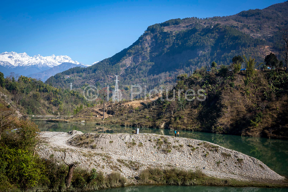 Young lovers stand holding hands on the banks of the Marsyangdi river on the 8th of March 2020  Lamjung District in Gandaki Pradesh, Nepal. The Marsyangdi river runs alongside the F036 highway that travels from Dumre to Besishahar in Lamjung, Nepal.