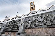 The Church of Nuestra Senora de la Asuncion peaks up from behind the massive sculpture: Evolution of the Totonac culture by Teodoro Cano Garcia, in the Plaza Central Israel Tellez Park in Papantla, Veracruz, Mexico.