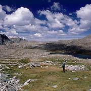 A lone backbacker crosses a high plateau in the Wind River Range of Wyoming.