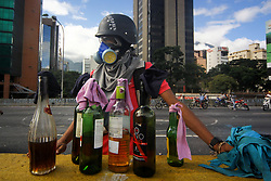 June 10, 2017 - Caracas, Capital District, Venezuela - protestor wearing helmet and gas mark, prepares molotov cocktails on the street. The Venezuelan opposition marched towards the avenue Victoria in the West of Caracas. The mobilization that was directed towards the Victoria avenue was attacked by troops of the National Guard Bolivariana (GNB ) That fired tear gas and shotguns at protesters. The protest culminated with several injured. (Credit Image: © Adrian Manzol via ZUMA Wire)