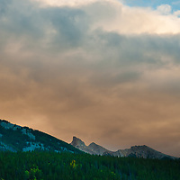 Sunset illuminates a crag & fall-colored forest in the Canadian Rockies.
