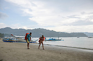 Two travelers with large backpacks walk in the rain on the beach in Port Barton, Palawan, Phillipines. (July 6, 2019)