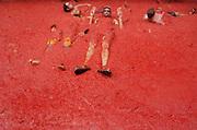 """V. 23. Valencia, 31/08/2005. Unos jovenes descansan en el tomate triturado durante la """"tomatina"""" de Buñol, Valencia, en la que cerca de 40.000 personas se han lanzardo durante una hora 120 toneladas de tomates maduros, una tradición que cuenta ya con 60 años de antigüedad. EFE/Kai Försterling."""