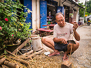 11 MARCH 2013 - LUANG PRABANG, LAOS: A man works in front of his colonial era shophouse in Luang Prabang, Laos. Luang Prabang is a UNESCO World Heritate Site and building renovations have to be done in a historically accurate way.     PHOTO BY JACK KURTZ