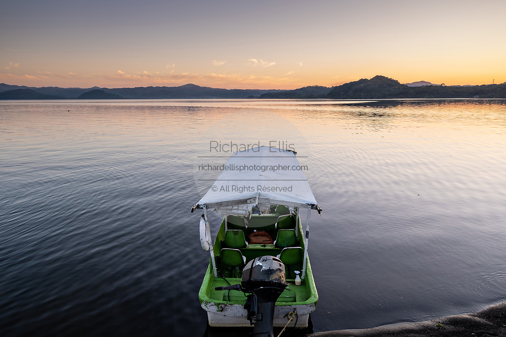 A tour boat along the shore of Lake Catemaco at sunset in Catemaco, Veracruz, Mexico. The tropical freshwater lake at the center of the Sierra de Los Tuxtlas, is a popular tourist destination and known for free ranging monkeys, the rainforest backdrop and Mexican witches known as Brujos.