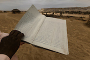 Tchicuteny?s family register book. In Angola?s Namibe desert, at Giraul, in the Namibe province, Tchikuteny, from the Mucubal tribe, is the leader of a big family, maybe the biggest family in the world.<br /> He is the chief leader, the manager and responsible for the entire village. <br /> In his village, Tchikuteny lives nowadays with most of his big family, his 33 wives, that were once 43, but 10 left the village, and most of their descendants.<br /> Tchikuteny maintains the registry of all the new-borns, totalizing 154 sons, and his grandsons, that are around 60. Nowadays, 4 new babies are on the way, and 3 great grand children were born recently.<br /> Huge harmony, love and respect transpire in the village atmosphere. The sense of a community is the pillar of their sustainability and sustenance and their autonomy depends prominently on cattle and agriculture that is made by the villagers. Nevertheless, Tchikuteny village is in close connection with their surrounding communities. Children attend Giraul School and there is proximity and relations with the extended family that lives in the surroundings.<br /> Being the spiritual leader of the community, Tchikuteny is also responsible for the weekly religious works that happens in the village church. <br /> This big family opened his doors to share with us their daily lives.