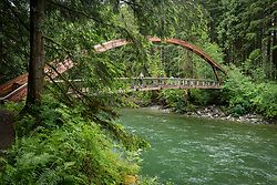 United States, Washington, North Bend. Arched suspension bridge over Middle Fork Snoqualmie River, in the Middle Fork Snoqualmie Natural Area, part of the Mountains to Sound Greenway.