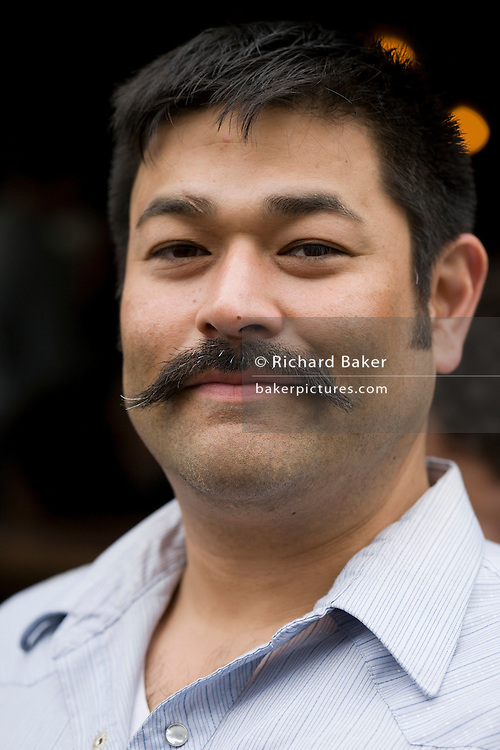 Young man in thirties street portrait with moustache.