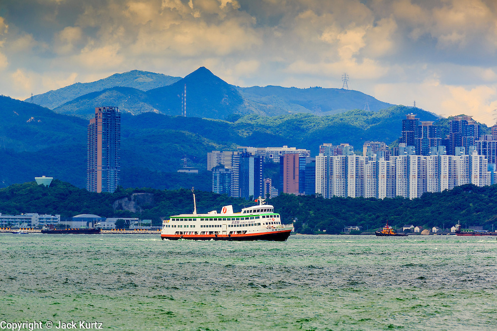 11 AUGUST 2013 - HONG KONG: A ferry crosses Victoria Harbor from Kowloon in Hong Kong. Hong Kong is one of the two Special Administrative Regions of the People's Republic of China, Macau is the other. It is situated on China's south coast and, enclosed by the Pearl River Delta and South China Sea, it is known for its skyline and deep natural harbour. Hong Kong is one of the most densely populated areas in the world, the  population is 93.6% ethnic Chinese and 6.4% from other groups. The Han Chinese majority originate mainly from the cities of Guangzhou and Taishan in the neighbouring Guangdong province.      PHOTO BY JACK KURTZ
