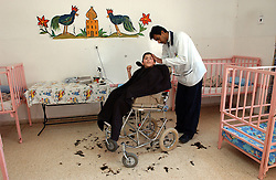 AZZARIYA, WEST BANK, MARCH 5: Mentally disabled, autistic and physically handicapped Palestinians and others who have no family or have been abandoned, find protection and receive compassionate treatment March 5, 2003 in Arba'at Batei Hahemla (Four Houses of Mercy) in Azzariya, West Bank. It was founded in 1940 by the late Palestinian philanthropist Catherine Siksek and is one place in the occupied territories where dozens of Palestinians and some of society's weakest members find care. Outside there is war, destruction, poverty and humiliation but inside it is a place of joy that none of the devastaton has been allowed to penetrate.  The doctors and nurses work grueling days for little pay and often spend 4 hours a day just to travel a few miles to get through Israeli checkpoints but it never deters them.